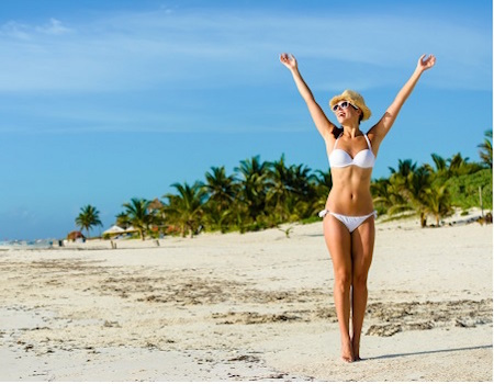 Beautiful blissful woman in white bikini enjoying tropical beach and caribbean summer vacation. Tanned brunette raising arms and enjoying freedom by the sea at Playa Paraiso Riviera Maya Mexico.